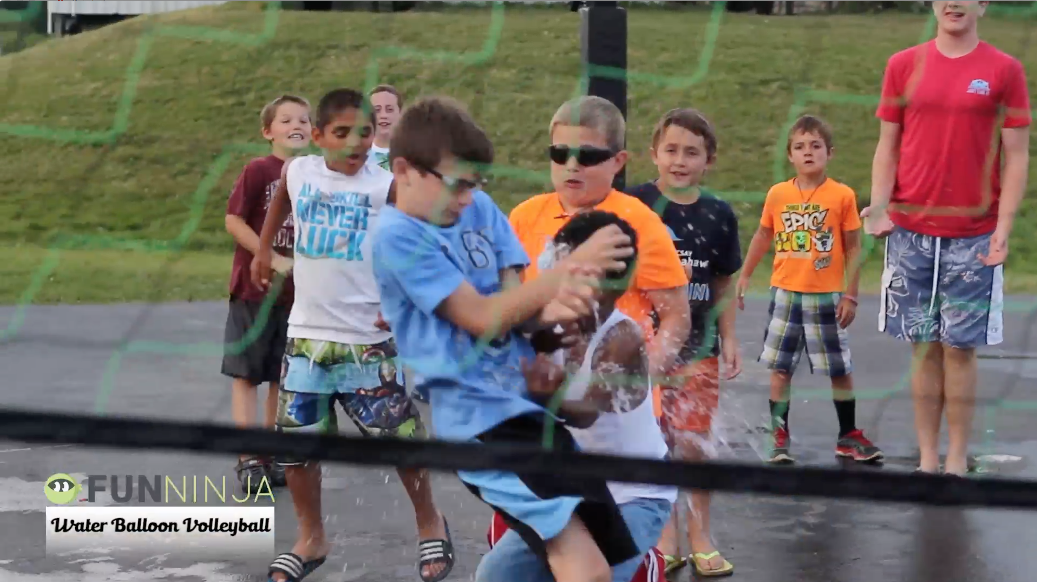 Student catching a balloon in water balloon volleyball; a Stuff You Can Use outdoor water balloon youth group game!